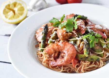 Delicious pasta with jumbo shrimps or prawns and green asparagus on a white plate. Healthy food on a white table or planks. Spaghetti Frutti Di Mare.