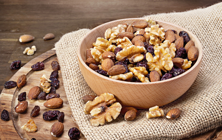 Delicious nuts arrangement in a wooden bowl. Close up shot of various nuts, healthy eating scene and wooden table. Stock Photo