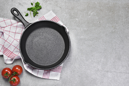 Cast iron pan on a grunge concrete background with copy space. Empty iron pan, top view or high angle shot with herbs and tomatoes.Cast iron pan on a grunge concrete background with copy space. Empty iron pan, top view or high angle shot with herbs and tomatoes. Фото со стока