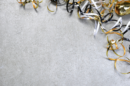 Christmas or holiday background with shiny gold ribbon on a white background. Celebration background with curly ribbon and copy space.