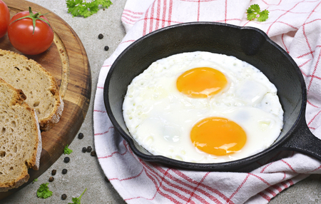 Delicious fried eggs in a cast iron pan. Top view of eggs and bread, breakfast scene. Фото со стока