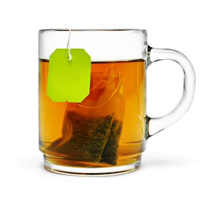 Cup of tea with tea bag and copy space, isolated on white background. Hot drink, herb tea or assam or earl gray tea. Cut out object.