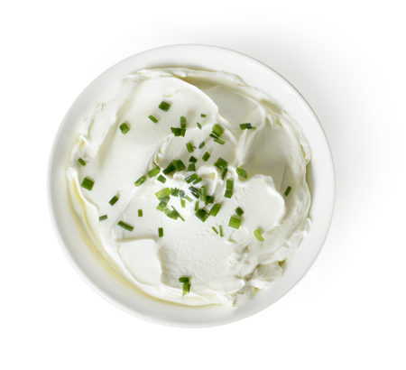 Cream cheese, quark or yogurt in a white bowl. Dairy product with fresh herbs, healthy eating theme. Isolated object on white background. Фото со стока