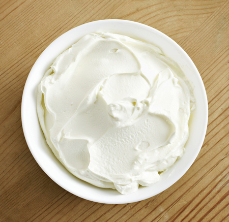 Cream cheese, quark or yogurt in a white bowl. Dairy product, healthy eating theme. wooden table background.