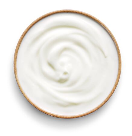 Delicious yogurt scene with wooden bowl, isolated on white background. Closeup shot of fresh healthy yogurt or cream. Top view. Banco de Imagens