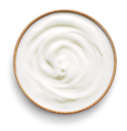 Delicious yogurt scene with wooden bowl, isolated on white background. Closeup shot of fresh healthy yogurt or cream. Top view. Standard-Bild