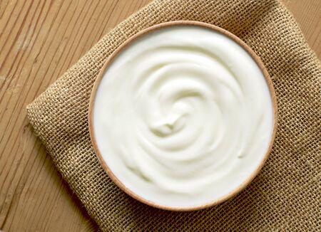 Delicious yogurt scene with wooden bowl and sackcloth. Closeup shot of healthy fresh yogurt. Top view. Banco de Imagens