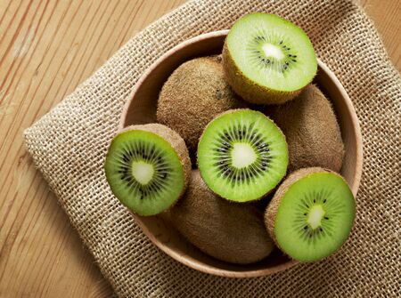 Delicious ripe kiwi fruits in a wooden bowl. Top view scene, healthy eating or healthy lifestyle. Cross sections of fresh kiwi. Standard-Bild