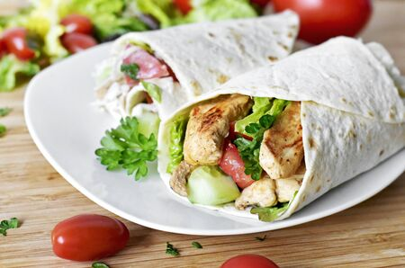Delicious fresh chicken wrap, closeup shot. Tasty tortilla with salad and turkey meat, healthy eating scene.