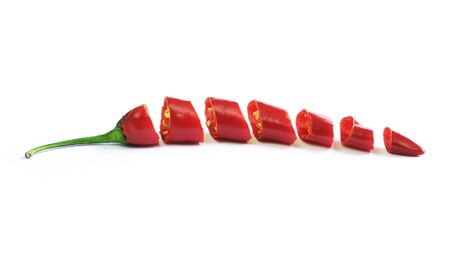 Red chilli pepper, cut into pieces and isolated on white background. Hot spice, red chilli pepper, cooking ingredient.