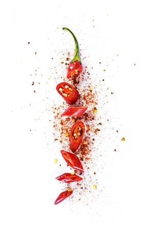 Red chilli pepper, cut into pieces and isolated on white background. Hot spice, red pepper and chilli powder.