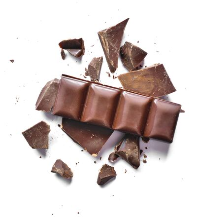Pieces of dark chocolate, isolated on white background. Delicious bitter chocolate, top view or high angle shot.