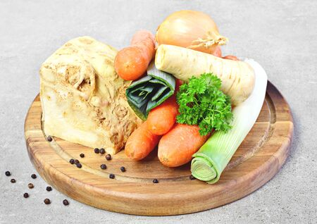 Soup vegetables, cooking scene. Broth ingredients, celery, parsley, leek and carrots on a wooden cutting board. Standard-Bild