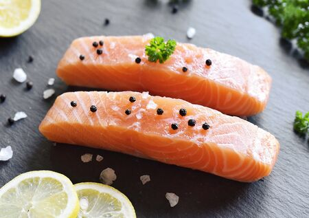 Delicious raw salmon fillet or sashimi on a slate plate. Fresh salmon and cooking ingredients. Close-up shot. Standard-Bild