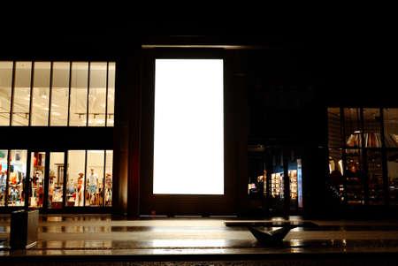 Scatola luminosa per segnaletica digitale vuota con ritratto alto all'aperto vicino a negozi al dettaglio e ristoranti presi di notte, ideale per poster di grandi dimensioni, enormi pannelli informativi e spazi pubblicitari di marketing.