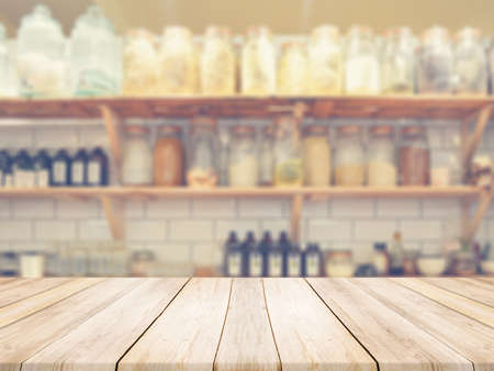 Light colored wooden table counter top at the kitchen with yellowish blurred condiments  background