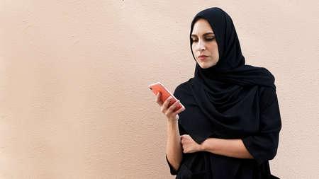 Arabic girl texting on her mobile phone smiling  wearing hijab Abaya 스톡 콘텐츠