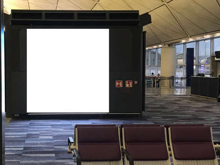 Large advertisement space light box inside an airport's departure waiting area with empty chairs