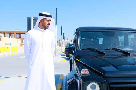 Local Arab man beside a 4x4 vehicle