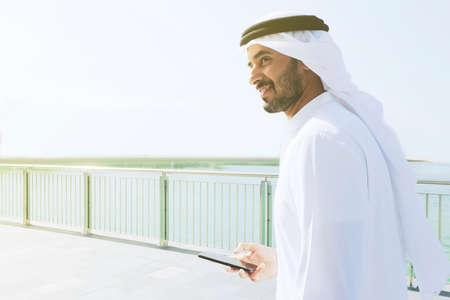 Feliz hombre árabe de Oriente Medio caminando sobre ladrillos vistiendo thawb kandura