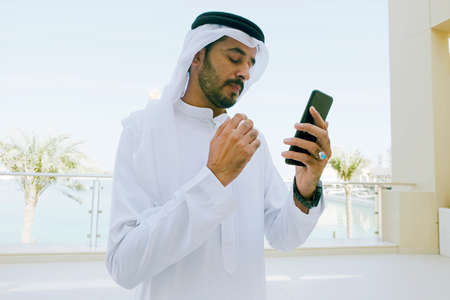 Middle Eastern Arab man using  mobile cell phone