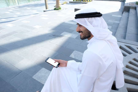 Local Arabic man pressing on his smart mobile phone mock up while at an outdoor location