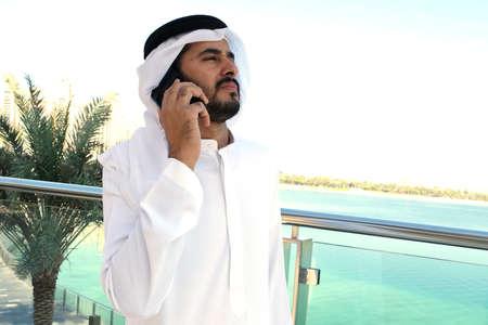 Arab Middle Eastern male model talking to phone wearing traditional dish dash gulf menswear