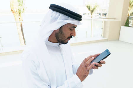 Middle East Arabian man using mobile phone touch screen doing online banking or eCommerce purchase
