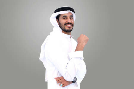 Handsome Happy Arabic Muslim man standing wearing traditional Middle Eastern menswear in the gulf called Kandura
