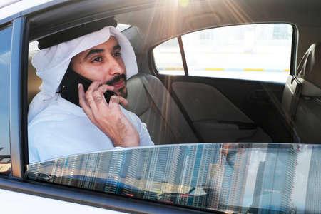 Arab Emirati man wearing kandora thobe while talking through his cellphone inside a car looking outside the window