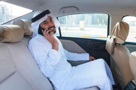 Local UAE Arab man talking on cellphone while riding a car backseat