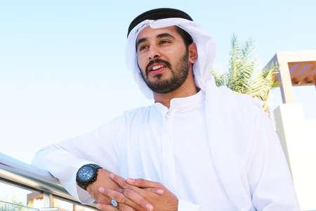 Happy handsome Arabian guy looking far and smiling wearing kandoora dishdasha