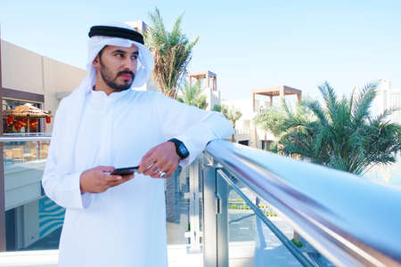 Rich Emirati man looking for away with mobile phone device wearing traditional middle east gulf men's wear kandora