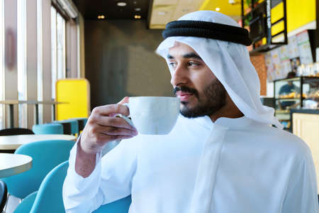 Close up of Arab man drinking coffee inside a cafe shop looking far outside through the window