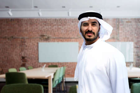 Arab man at modern office looking straight with positive outlook