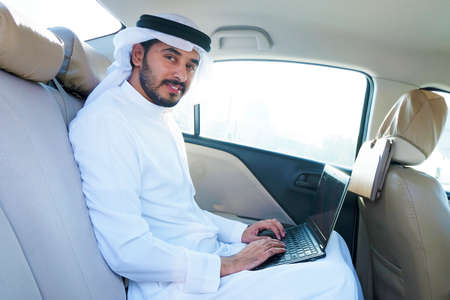 Local Arabic business man using laptop while inside a car vehicle
