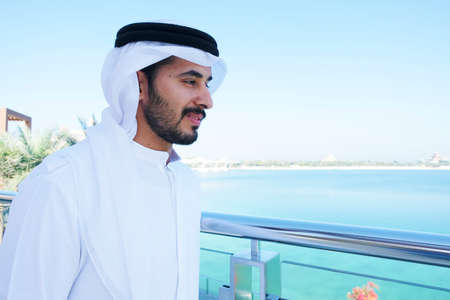 Inspired and happy  Arabic emirati man with positive mind wearing dish dash kandura, a traditional menswear in the Middle East which includes UAE and Saudi Arabia