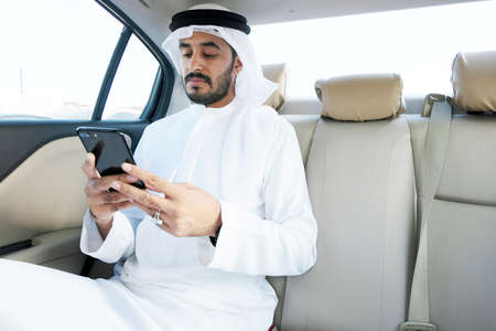 Optimistic Arabian business man reading the news about the market, trends or economy update in the Middle East. 스톡 콘텐츠