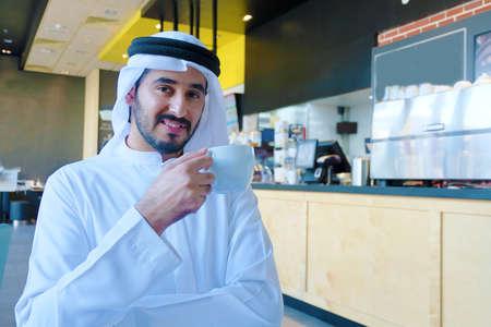 Middle Eastern Arab man drinking coffee inside a cafe