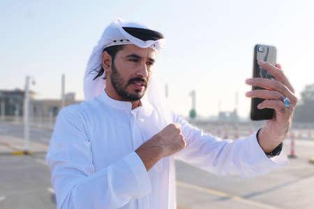 Middle Eastern Emirati Arab model fixing his traditional menswear garment Ghutra using his phone