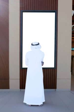 Arab man looking on blank light box copy advertisement space ideal for mock up, digital signage, information board, posters or video marketing