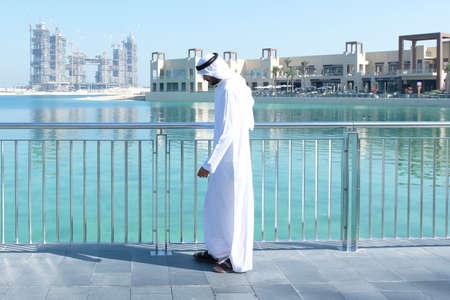 Walking local UAE emirati man walking outdoors  wear Arab menswear called Kandura