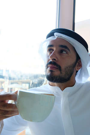 Arab man with coffee cup looking up  wearing Ghutra 스톡 콘텐츠