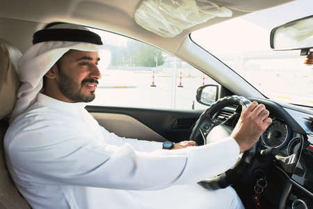 Hombre árabe musulmán conduciendo dos manos en el volante mientras se centra en la carretera