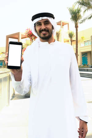 UAE Arab man holding his mobile phone ideal for smartphone mock up