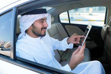 Middle Eastern Emirati man texting inside a car wearing traditional  Arabic kandoora thobe menswear in UAE 스톡 콘텐츠