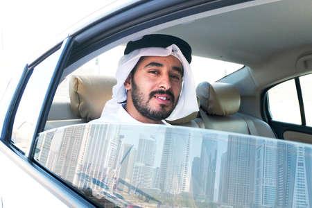 Pasajero masculino árabe feliz mirando desde la ventana de un coche mientras sonríe durante un día soleado Foto de archivo