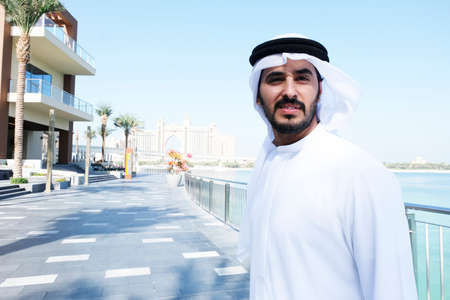 Local Arabian business man smiling while outdoors wearing traditional cultural kandora men's wear
