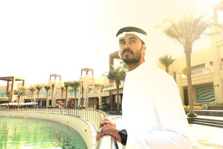 Guapo chico árabe vistiendo kandoora dishdasha durante la puesta de sol