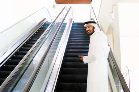 Emirati Arab guy on elevator wearing cultural kandura dress for men